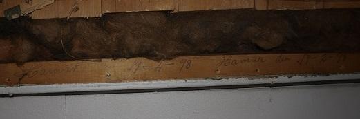 En liten hilsen fra husets byggeår skrevet på en lekt over døra.